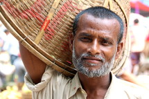 Bangladeshi man with a basket in the market.