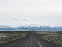 rural road and snow capped mountains
