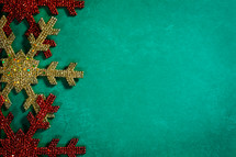 gold and red snowflake ornaments on a green background