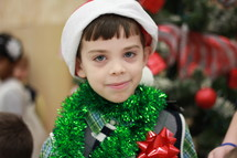 A little boy wrapped in Christmas tinsel.