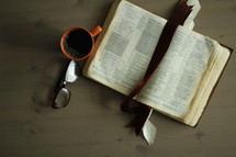 an open Bible, coffee mug, and reading glasses on a coffee table