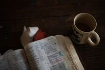 notes on the pages of a Bible and a coffee mug on a table