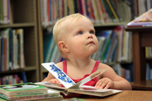 a toddler girl reading a book in a library