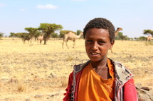 Ethiopian herdsman in Ethiopia with camels in the background tribe tribal savannah desert ragged clothes tribesman amharic tigrinya