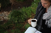 a woman standing outdoors in a scarf holding a mug and reading a Bible