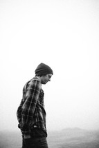 man in a wool cap standing in the fog