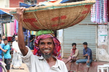 Bangladeshi man with a basket on his head in the market