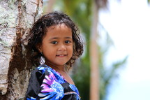A young polynesian girl with curly hair, leaning against a tree, dressed for Church