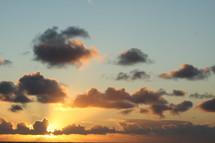 sun glowing behind clouds