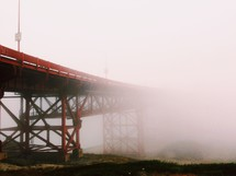 An orange bridge covered in fog.