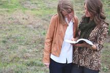 women standing outdoors reading a Bible