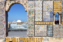 View of a domed mosque in an Arab city in North Africa through a decorative tiled archway.