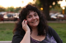 A smiling woman talking outside on a cell phone.