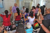 Hands raised in praise at a worship service in a small church in Havana, Cuba