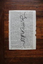 surrender written on the pages of a Bible