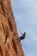 Woman rappelling after climbing steep mountain face