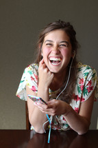 A girl listening on ear phones and laughing.