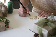 a woman writing on gift tags