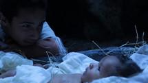 adoring eyes and baby Jesus in a manger