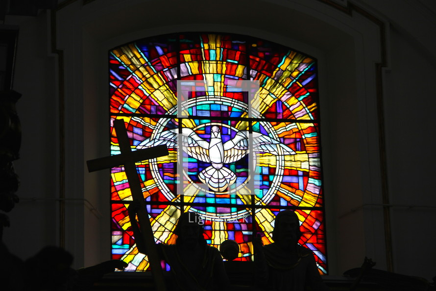 Stained glass window depicting the Holy Spirit descending like a dove with silhouette of man holding christian cross