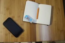 open journal, cellphone, pencil, and eraser on a desk