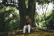 teen girl sitting under a tree