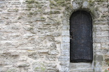 Arched door and doorway in an ancient stone wall