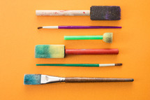 paint brushes on yellow