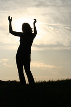 Woman outdoors with raised hands looking to the sky