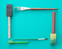 paint brushes on teal