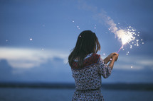 woman holding a sparkler outdoors