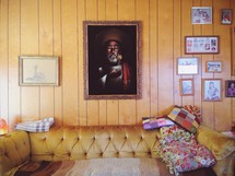 Painting of Christ hanging on a paneled wall, surrounded by family photos, in a den with a velvet sofa covered in quilts.