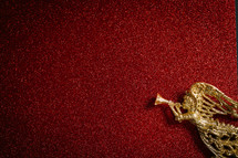 gold angel ornament on a red glittery background