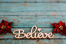 poinsettias and word believe on teal wood background