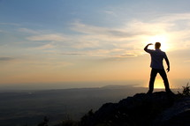 a man looking out at the view standing on a mountain top at sunrise/sunset
