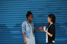 friends talking in front of a blue wall