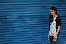 a young woman standing in front of a blue wall