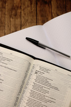 pens, notebook, and open Bible at a Bible study