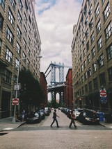 A crosswalk and a view of the Brooklyn Bridge.