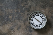 Antique magnetic compass on stone table