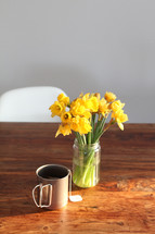 daffodils in a jar and mug of hot tea