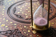 Sand measuring time running through an antique hour glass on oriental desk