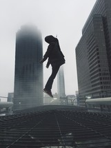 man leaping in a foggy city