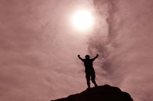 Silhouette of a man with his hands raised in the air in victory after climbing tall mountain