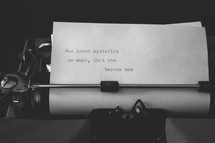 An old manual typewriter with a line of text typed on the paper.