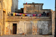 clothes drying on a clothes line across two buildings in an old building