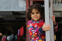 A smiling young Chaldean Christian girl and a clothes on a clothes line in a refugee camp in Iraq. [For similar search Ethnic Smile Face].