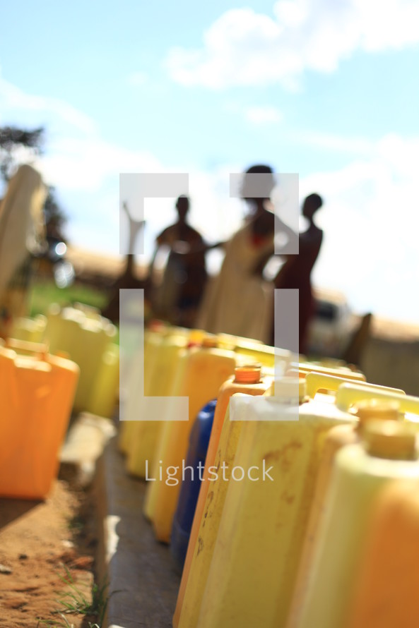 row of water canisters in Africa