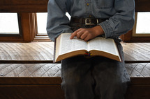 a boy sitting reading a Bible