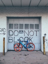 """A bicycle leaning against an overhead door reading """"Do not block"""" and """"No parking."""""""
